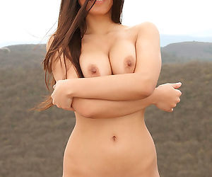 Perky boobs Asian walks along the rock and takes her clothes off