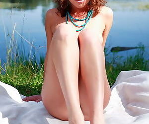 Nude chick outdoors with small perky tits and a trimmed pussy