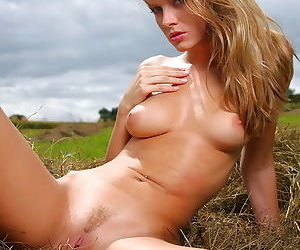 She lies in the hay in the field and she opens her legs to show pussy