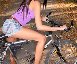 Great tits and shiny lips on the pretty Asian chick on a bike outdoors