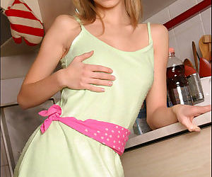 Young blonde teen takes off her clothes in the kitchen