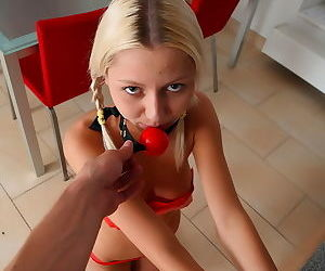 Cute blonde teen in a ball gag and tape over her titties is having fun