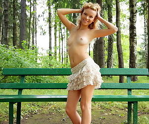 Shaved tight blonde girl outdoors smiles as she poses in the forest