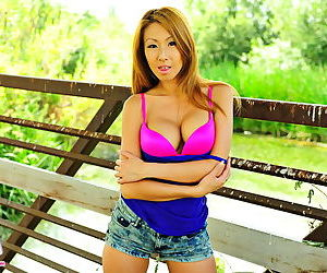 Sporty Asian strips outdoors and lays her arm across her big tits