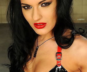 Black latex lingerie and luscious red lips look great on solo model Honey Demon