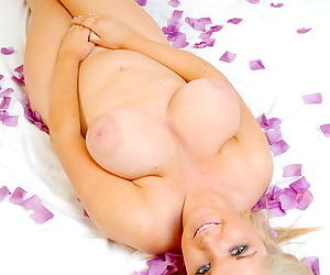 Full blonde kitty with huge jugs hides her pussy under flower petals