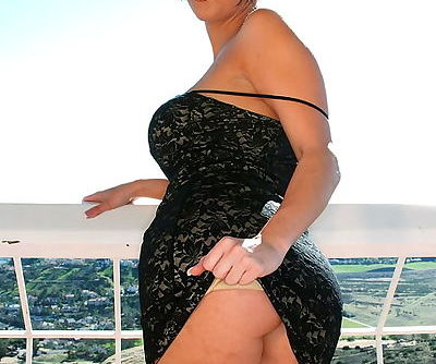 Stripping from a black lace dress as she stands on the deck