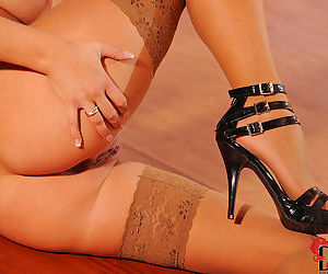 Graceful angel in brown stockings is rubbing her shaved pussy on the floor indoors