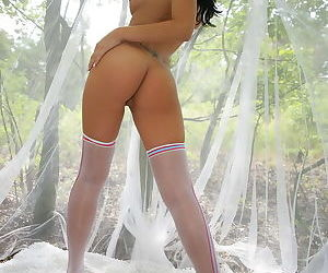 She wears stockings and she opens her legs to model her naked pussy