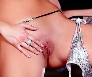 A redhead in boots wears a shiny lingerie set and fingers her tasty shaved pussy