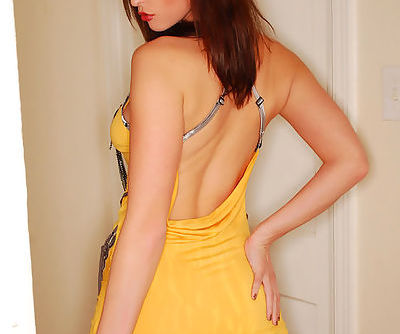 Innocent and sexy brunette babe in yellow dress is showing her small natural tits indoors