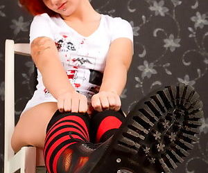 Horny redhead with a red dildo pushes it into her pussy as she wears socks