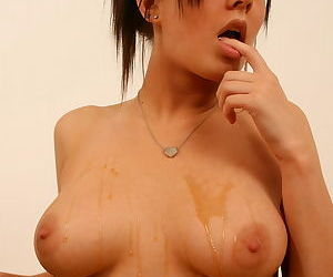 She pours a little bit of honey on her naked tits to make you dream of licking