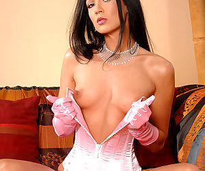 Awesome and pretty brunette in pink gloves is fingering her shaved pussy on the sofa