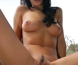 Girl lies on a blanket outdoors and spreads her legs to show young pussy