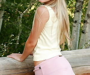 Young and cute she sits on a log outdoors and models her fresh pussy