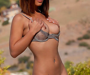 Petite solo Asian in high heels strips down to just her bra and poses outdoors