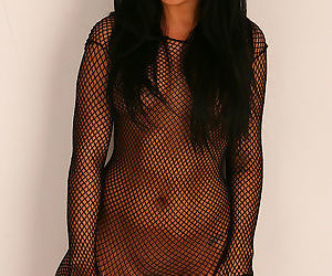Arousing brunette enjoying posing her nude body througn one sexy fishnet costume