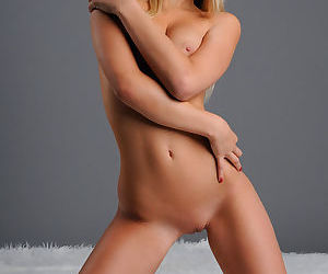 Blonde in erotic art gallery has perky tits and a bald pussy