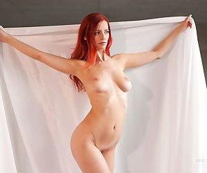 Amazing redhead with natural tits and a trimmed pussy poses nude