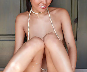 This Asian babe is pretty and she poses naked with only a pearl necklace