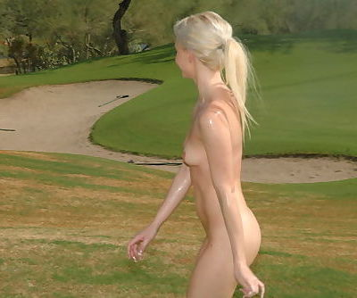 Cute blonde girl is walking the golf course and happily taking her clothes off