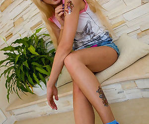 Teenage bodyart junkie spreads her long legs showing trimmed snatch