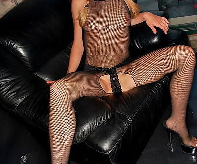 Naughty young blonde honey poses in crotchless black fishnet overall