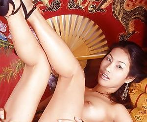 Asian babe teases her hairy pussy and big tits while playing with toys