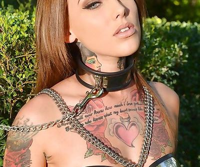 Inked fetish model undergoing outdoors slave training in collar