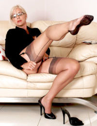 Fully clothed older businesswoman slips off pumps to reveal stocking feet - part 2