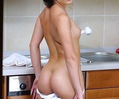 Smiley brunette cheerleader undressing and exposing her goods in the kitchen
