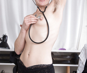 Mature brunette Sunshine shedding doctor garb before exposing hairy twat