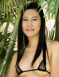 Young Asian girl with firm tits slips off her string bikini amid lush greenery