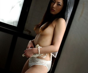 Japanese dame Ran Asakawa removes washed out bra and undershorts by an honest window