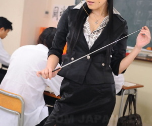 Japanese schoolteacher Yui Komine monitors students with pointer with reference to hand