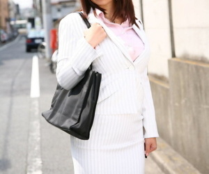 Fully clothed Japanese engrave Sayuri Mikami walks the street in a business harmonize