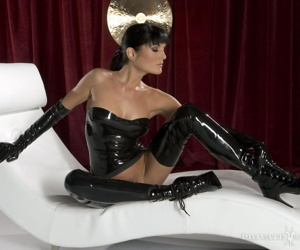 Dark haired femme fatale displays her ass and twat in latex attire