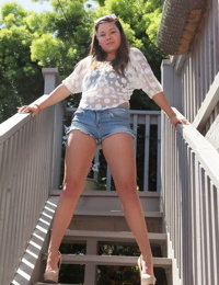 Shapely teen Nikki Yann bares round ass in thong panties & sheer shirt outside