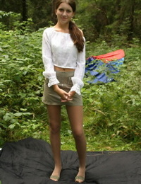 Thin teen frees long hair from ponytails after disrobing in the woods