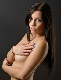 Dark haired solo girl Shana Lane covers her naked breasts with her hands