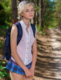 Young looking girl Azshara strips off school clothes on a dirt road in woods
