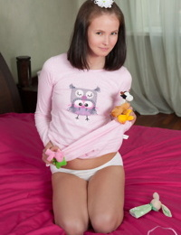Cute teen Candy stands totally naked after undressing atop her bed