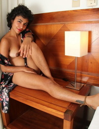 Exotic solo model with long legs and black hair reveals her bush in motel room