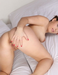 Brunette amateur Lucy Kringle plays with her twat after getting naked on a bed