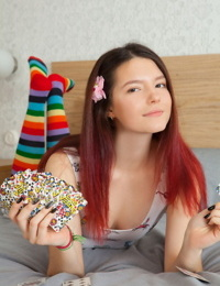 Young looking redhead Diana removes striped OTK socks to pose fully naked