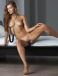 Young Russian girl with a nice smile poses her tan lined body in the nude