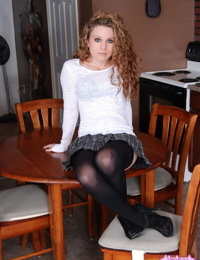 Young looking girl with wavy hair strikes tempting sfw poses on kitchen table