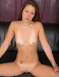 Young redhead releases tan lined body from lingerie to pose naked on couch