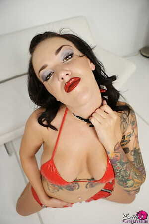 Tattooed chick Emily Parker wears a collar while deepthroating a cock